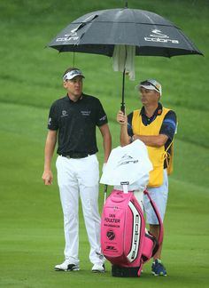 Ian Poulter of England waits with his caddie Terry Mundy on the tenth hole during the second round of the 95th PGA Championship on August 9, 2013 in Rochester, New York.