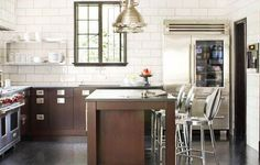 Kitchen with subway tiles walls,dark brown wood lower cabinets with matching island, stainless appliances and metal pendant lights