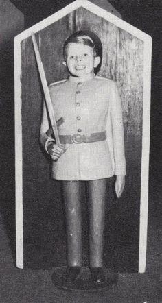 young David Bowie (posing in a stick-your-head-through facade)