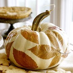 decoupage leaves onto painted pumpkin...darling. can use faux pumpkin and fabric for keeps too.