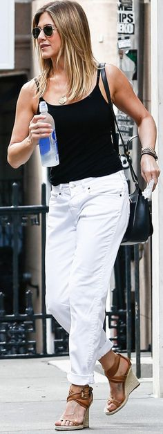 Who made Jennifer Aniston's gold jewelry, jeans, sunglasses, black handbag, tank top, and brown wedge sandals?