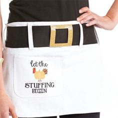 """Cotton apron with pilgrim belt features gold buckle and turkey pocket that reads, """"Let the stuffing begin""""."""