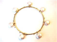 A handmade 18 karat yellow gold bangle bracelet studded with seven coin pearl charms. Jingle Jangle! A Mrs. Jones & Co. original.  The bracelet measures approximately 3 inches in diameter.