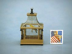 Brass bird cage with canary on a swing.