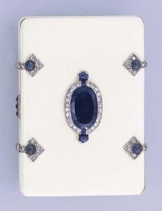 AN ART DECO SAPPHIRE AND DIAMOND VANITY CASE. The small rectangular cream enamel case with central oval-cut sapphire in diamond surround to the sapphire and diamond-set clasps opening to reveal a compartment, lipstick holder and mirror, chip to enamel near sapphire push piece, circa 1920, 5.9 cm. wide, with French assay marks for silver and gold.