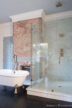 Tour of 1905 Historic Home Restoration! Our vintage modern master bathroom reveal... white-marble-clawfoot-tub-antique-brass-bath-antique-brass-fixtures-lantern-wall-mount-faucet-fable-sconce-thick-marble-apron-countertop-marble-wall-tile-alabaster-walls-blue-ceiling-brick-fireplace-glass-shower-enclosure-natural-wood-cabinets-flat-panel-waterfall-counter