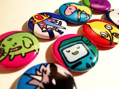 """HUGE Adventure Time 1"""" Button Set - UNACCEPTABLEEEE            NEW and IMPROVED! Now with EIGHT more buttons than before for a total of SIXTEEN 1"""" buttons! What the plop?!    Get those sweet buns over here!    Here we have 16 denizens from the land of Ooo. There's the genderbend kiddos too! How totally math. These are totally perfect for stocking stuffers! Probably not sock stuffers though because they have pointy bits on the back.    Sixteen 1"""" buttons to a set!    Finn  Jake  Princess…"""