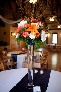 Get rid of the fern, and replace it with another green, replace orange Lillie's with another flower.  Orange & Navy Blue Wedding at Amber Springs| Photo by: jwbaugh.com