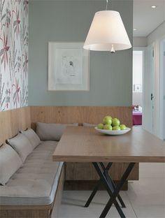 Um recurso para dar a impressão de que a sala é maior foi a definição de dois papéis de parede diferentes, criando um contraponto entre a estampa vibrante de flores e a sobriedade das listras douradas sobre o fundo verde. No jantar, a estrela é a gravura de Picasso emoldurada pela Struttura Arte Moldura. Com 1,60 m x 80 cm de largura, a mesa é deslocada facilmente. Papéis de parede da Villa Nova e pendente da Lumini.