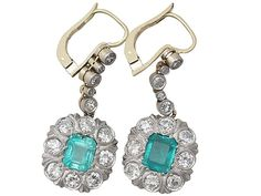 2.56 ct emerald and 1.65 ct diamond partner together to forge these antique 18 ct yellow gold cluster drop earrings.