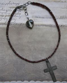 *** This item is RESERVED for B. thank you! ***  25 mars 1920 . necklace A wonderful antique French nun cross delicately hangs from a necklace of micro faceted garnet rondelles. The cross is made of silver and it is engraved at the front and back with the date and the family name of the nun. A lovely antique French glass heart charm with the figure of our Lady and Lourdes adorns the back. Very delicate and feminine. It looks really nice when layered with other necklaces, as shown in the…