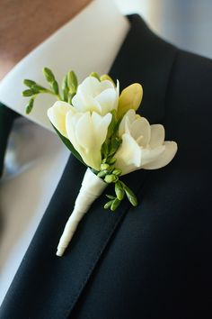 boutonniere of white freesia wrapped in a band of ivory ribbon