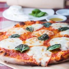 This stone baked Margherita pizza recipe is amazing! The pizza is made with homemade tomato sauce, buffalo mozzarella & fresh basil