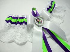 White Satin with Purple Satin and lime Green Trim with White Lace Skirt. White Satin Bow with Satin Ribbon Ties in Purple and Lime Green and Silver Crown/Glass Top with Buzz Lightyear inside. Purple Satin, White Satin, Diy Wedding, Dream Wedding, Wedding Dreams, White Lace Skirt, Toy Story Party, Wedding Garter, Satin Bows