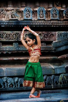 Bollywood influenced. The little girl captured in this photograph is performing Bharat Natyam, a classic Indian dance form.