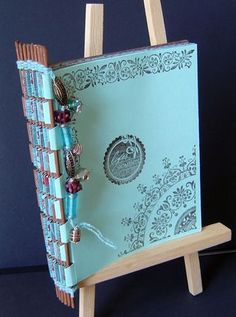 Piano hinge book tutorial - so interesting! Uses cardstock and skewers, plus a bit of thread at the ends. Beads for decorating. In place of skewers you can try artificial flower with a long stem, chopsticks, maybe even pipe cleaner/chenille stems.