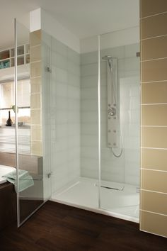 White large format glass tiled shower with a beige glass tile border.