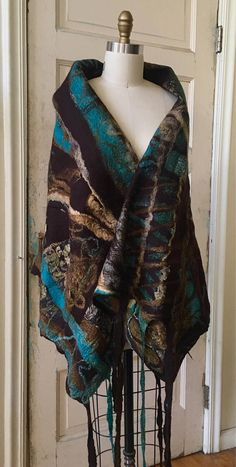 This shawl is made with primarily brown, turquoise and deep gold fine merino wool, silk blended merino, and silk. It has long felted brown and gold tasseled dreads on the ends (the width sides) of the shawl. It is light and it drapes well because of the silk. It is also warm and