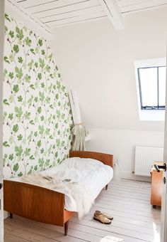 Old-fashioned look in the kids room with a bed of teak-wood and wallpaper with green fig leaves.