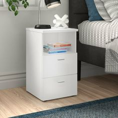 Simple and streamlined but with plenty of storage for your bedside essentials, this table includes an open shelf and two drawers. It is made from manufactured wood with a highly scratch-resistant melamine coating. Assembly is required.