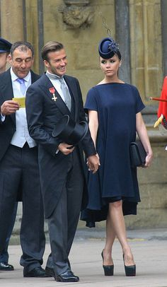 Victoria Beckham in a navy blue dress from her Victoria Beckham Collection, custom Christian Louboutin heels, and a Philip Treacy fascinator.