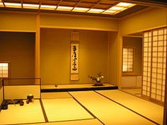 Interior view of a large tea room with tatami and tokonoma. Seen in the tokonoma is a hanging scroll, flower arrangement (not chabana style), and incense burner.