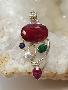 Handmade multi-gemstone pendant with large oval-shaped faceted Indian Ruby center stone, adorned with 1 sapphire, 1 faceted emerald, and 1 pearl, and a pear-shaped ruby gemstone hinged dangle, set in