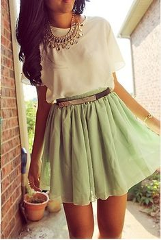 Light silk blouse with statement necklace and light green skirt with black and gold belt.