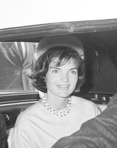 Portrait of Jacqueline Kennedy Wearing a straw pillbox hat and a pale blue silk dress, Mrs. Kennedy smiles from the rear seat of an auto as she and the President head home after attending Easter Sunday services