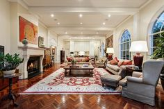 Great use of a very large living room with a kitchen overlooking.  Stunning herringbone parquetry floors.  The art above the fireplace is effective in breaking the space in two.