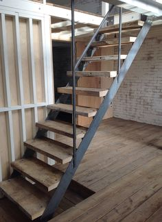 Reclaimed treads on bespoke steel staircase, reclaimed Victorian pine flooring, exposed framing with silver birch plywood hinged wall panels. Decorating with finishing. Warehouse conversion. Leyton E10, London