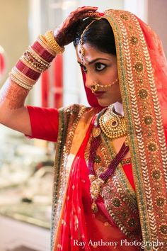 Indian bride wearing bridal lehenga and jewelry. #BridalHairstyle #BridalMakeup