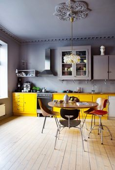 Yellow base cabs with a charming hodgepodge of wall cabinets and decorative moldings, unified by color.