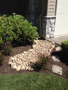 Ditch the ugly concrete downspout trough and add a flowing river rock drainage field, just remember the landscape cloth to prevent weeds!