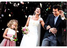 Fotografía de bodas Fotografía en color de los novios saliendo por la puerta entre arroz y pétalos de flores