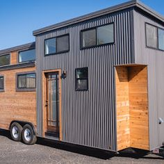 A modern tiny house with a bright, modern interior. The 20 ft home has a full kitchen, living room, bathroom, and a loft bedroom.