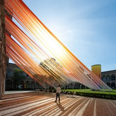 """Invisible Border"" is an installation by MAD Architects in Milan, Italy. - photo by Moreno Maggi, via dezeen;  At the Cortile d'Onore courtyard at the Università degli Studi di Milano, ""lengths of ETFE plastic [are] stretched from the 15th century building down to the grassy square below. ... A wavy metal frame is used to hold the strips taught, forming an extension of the building's covered passages for visitors to walk under."""