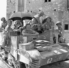 Infantrymen of the Edmonton Regiment in a Universal Carrier, using an umbrella to provide some shade, Valguarnera, Italy, July 17, 1943.