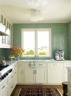 White and green kitchen features white shaker cabinets paired with white marble countertops and a green mosaic tile backsplash. A brown kitchen rug leads to a sink and adjustable faucet placed under windows lit by white flush mount lights.