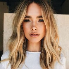 Soft blonde hair waves and natural makeup for beauty inspiration.