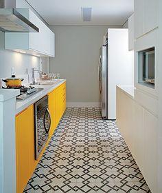 """Os moradores queriam uma cozinha colorida, mas que não cansasse. """"Optei pela laca brilhante amarela só nas portas do armário sob a bancada e deixei branco o de cima, na altura da visão"""", explica a arquiteta Andrea Reis. Para destacar a marcenaria, ela pintou a parede de cinza claro e revestiu o piso com ladrilho hidráulico estampado de cinza escuro"""