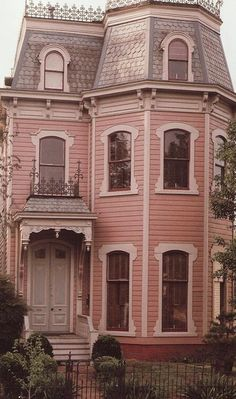 Pink House victorian, with a mansard roof, fish scale shingles, and roof cresting