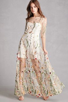 A sheer woven mesh maxi dress featuring an allover colorful garden embroidery with flowers, foliage and butterflies, an illusion neckline, sheer 3/4 sleeves, a mini lining, and a hidden side zipper.