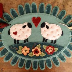 "A Sweet pair of plump Lambs sharing their Love on a texture filled Wool Applique. Raised edges on the Flowers and Leaves plus the many ""Lamb's Tongues"" circling the oval topper add plenty of Applique interest!"