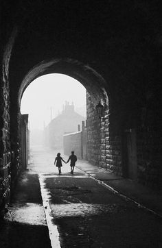 a boy and a girl hold hands under an archway in the gorbals, a slum district of glasgow, january 31, 1948