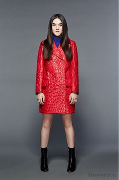 """Isabelle Fuhrman of """"Masters of Sex"""" wears a red patent faux leather Miu Miu car coat, blue turtleneck, and patent ankle boots"""