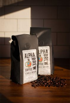 two alpha brew coffee bags with beans spilled on butcher block countertop with sunlight on a subway tile backsplash, photographed by jamie bannon photography. Advertising Photography, Photography Branding, Commercial Photography, Photography Office, Photography Kids, Wedding Photography, Photography Accessories, Photography Website, Coffee Branding