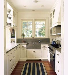 Lovely white kitchen with good and shelf above stove. And a great sink.