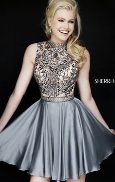 Achieve the next level of sophistication in Sherri Hill 1965. This cocktail dress showcases a high neckline. The nude inlay is fully coated with patterned beading creating a teardrop opening at the back. The short skirt flows smoothly down the mid-thigh hem.