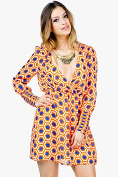 A demure double surplice dress with a colorful, op art-inspired body. Pleated detail at cuffs. Single strap across back. Chiffon body. Lined.